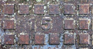 Rostiger Kanaldeckel mit rechteckigem Profil und prägeartiger Nr. 15 Lizenzfreies Stockbild