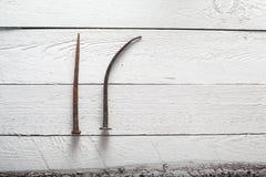 Rostiger Nagel auf weißem hölzernem Hintergrund Stockbild