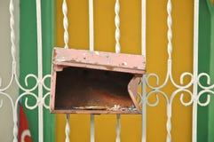 Rostiger roter gebrochener Briefkasten hing an einem Zaun Stockfotos