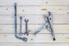 Rostiger Schlüssel und Blockierungszangen auf weißem Holz Lizenzfreies Stockbild