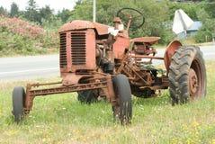 Rostiger Traktor, der auf dem Straßenrand oxidiert stockfotos