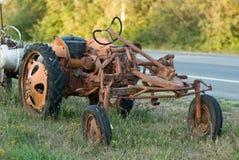 Rostiger Traktor, der auf dem Straßenrand oxidiert lizenzfreies stockbild