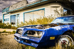 Rostiges Auto durch Tankstelle Stockfotografie
