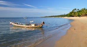 Rostiges Boot des langen Hecks auf der Sandküste Stockfoto