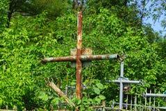 rostiges Eisenkreuz überwältigt mit grüner Vegetation an einem Kirchhof stockbilder