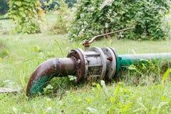 Rostiges grünes altes Rohr mit Ventil auf dem grünen Gras stockfoto