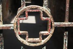 Rostiges Kreuz auf Stangentür Stockfotos