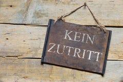 Rostiges Metallschild auf Holztisch, deutscher Text, Konzept kein Eintritt Stockbilder