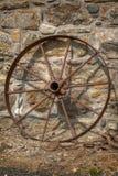 Rostiges Wagenrad, das gegen eine Steinwand nein stillsteht 2 lizenzfreies stockfoto