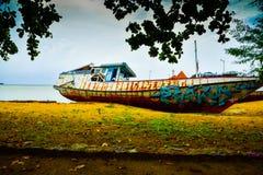 Rostigt övergav den gamla fiskebåten som lämnades på stranden royaltyfria bilder