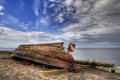 Rostigt fartyg som vänds som är uppochnervänt på sjösida Royaltyfri Foto
