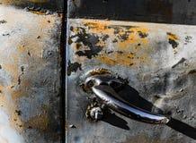 Rostigt, gammalt kastat bildörrhandtag i träna Fotografering för Bildbyråer