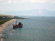 Rostigt skepp som sköljas upp på stranden av kusten av Grekland royaltyfria bilder