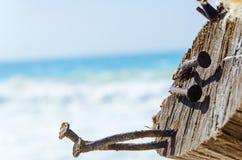 Rostigt spikar i ett stycke av trä på stranden Arkivbilder