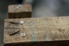 Rostigt spikar och brunt trä royaltyfri bild