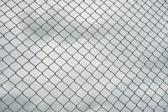 Rostigt staket för ståltrådingrepp, moln i bakgrund royaltyfri bild