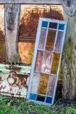 Rostigt tenn- och målat glassfönster arkivfoto