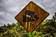 Rostigt vägmärke - kall nedstigning i hål från kulor Arkivfoton