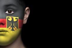 Rosto humano pintado com a bandeira de Alemanha foto de stock