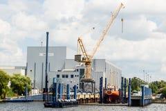 ROSTOCK, ALEMANIA - CIRCA 2016: Una grúa ayuda a la construcción de un yate en el pequeño astillero en el puerto de Rostock en Al fotografía de archivo libre de regalías