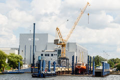 ROSTOCK, GERMANY - CIRCA 2016: A crane assists the construction of a yacht at small shipyard at the harbor of Rostock in Germany.  Royalty Free Stock Photography
