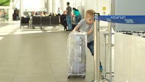 ROSTOV-ON-DON, FEDERACIÓN RUSA - 22 DE MAYO DE 2019: Niño con una maleta en aeropuerto almacen de metraje de vídeo