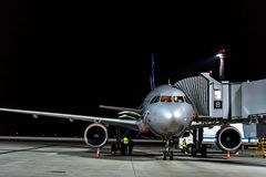 ROSTOV-ON-DON, RUSSIA - 28 APRIL 2018: Jet bridge and plane in Platov airport. ROSTOV-ON-DON, RUSSIA - 28 APRIL 2018: Evening view of plane and attached jet Stock Photos
