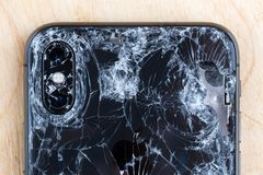 Broken iPhone XS lies on a wooden surface. royalty free stock photo
