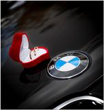 Rostov-on-don, Russia, 06/07/2014: gold wedding rings in a red velvet box. On the black hood of the car with the BMW logo royalty free stock image