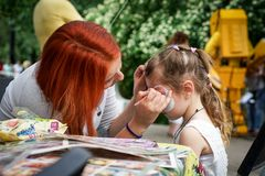 ROSTOV-ON-DON, RUSSIA - MAY, 2017: Animator drawing a cat makeup on the face of a girl. Children holiday, party concept.  royalty free stock image
