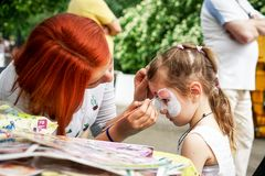 ROSTOV-ON-DON, RUSSIA - MAY, 2017: Animator drawing a cat makeup on the face of a girl. Children holiday, party concept stock image