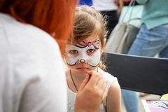 ROSTOV-ON-DON, RUSSIA - MAY, 2017: Animator drawing a cat makeup on the face of a girl. Children holiday, party concept.  royalty free stock photos