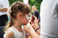ROSTOV-ON-DON, RUSSIA - MAY, 2017: Animator drawing a cat makeup on the face of a girl. Children holiday, party concept.  stock photo