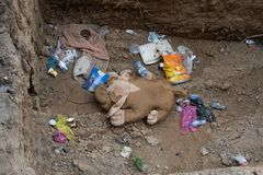 Rostov-on-Don, Russia - May 18, 2018: Toy dog abandoned in pit with garbage. Homeless concept. royalty free stock images