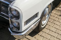Dual front headlights of a vintage white Cadillac Coupe de Ville at retro cars show. ROSTOV-ON-DON, RUSSIA, 07 OCTOBER 2017: Dual front headlights of a vintage stock photo