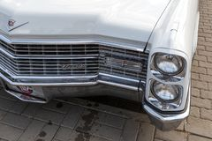 Headlights and radiator grill of a vintage white Cadillac Coupe de Ville at the retro car show. ROSTOV-ON-DON, RUSSIA, 07 OCTOBER 2017: Headlights and radiator stock photos