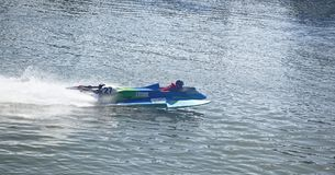 Racer on the speed boat rushes in front of the audience at the Stock Images