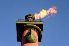 Rostral column with a fiery torch. Rostral column with a fiery torch on blue sky background in Saint Petersburg, Russia Royalty Free Stock Photos