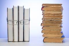 Rostro humano hecho de algunos libros con los vidrios, con la pila de libros lamentables viejos El concepto de lectura fotos de archivo