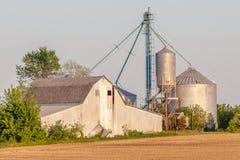 Rostscheune und -silos im Landwirtschaftsackerland Stockfotografie