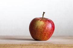 Rosy apple. Ripe red apple on wooden kitchen board with light background Royalty Free Stock Images