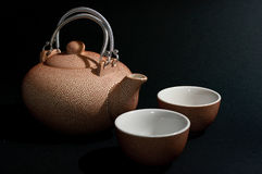 Rosy teapot. Rosy ceramic teapot and cups on black background Stock Image