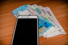 Rosyjscy banknoty i telefon komórkowy na drewnianym stole zdjęcia stock
