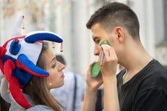 Rosyjski dziewczyna wielbiciel sportu w kolorowej kapeluszowej rysunkowej brazylijskiej flaga na policzku brazylijski mężczyzna Zdjęcie Royalty Free