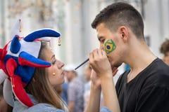 Rosyjski dziewczyna wielbiciel sportu w kolorowej kapeluszowej rysunkowej brazylijskiej flaga na policzku brazylijski mężczyzna Zdjęcia Royalty Free