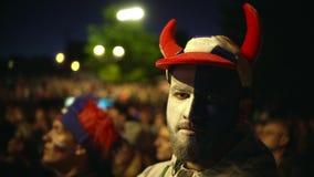 Rosyjski fan zamknięty w górę nieradej złej gry, patrzeje kamerę 4K z farby twarzą zdjęcie wideo