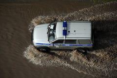 Rosyjski samochodu policyjnego jeżdżenie przez zalewającej ulicy po silnej prysznic obrazy royalty free