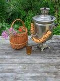 Rosyjski samowar na nieociosanym drewnianym stole z jagodami i kwiatami Zdjęcie Royalty Free