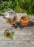 Rosyjski samowar na nieociosanym drewnianym stole z jagodami i kwiatami Zdjęcia Stock