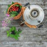 Rosyjski samowar na nieociosanym drewnianym stole z jagodami i kwiatami Zdjęcie Stock